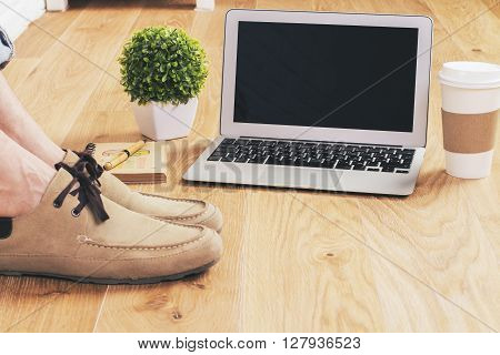 Male feet on wooden floor next to blank laptop screen coffee plant and other items. Mock up