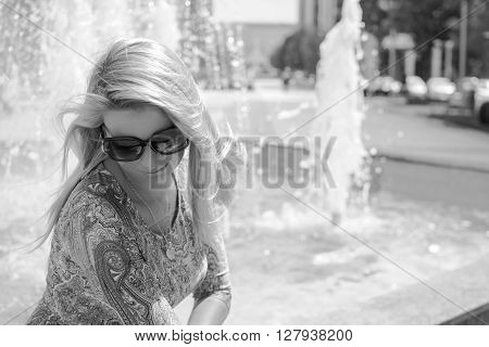 Beautiful woman with long blonde hair and black glasees, near fountain splash