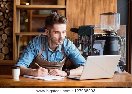 Involved in writing. Pleasant concentrated handsome  barista making notes and using laptop while standing at the counter
