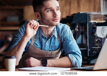 Let me think. Pleasant handsome content thoughtful barista thinking and making notes while using laptop