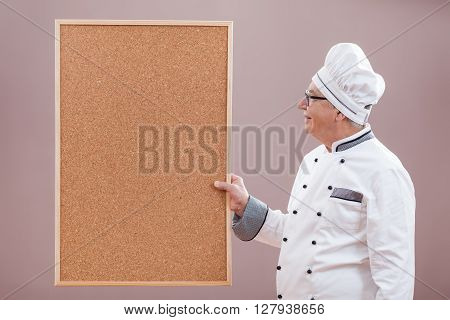 Portrait of restaurant's chef in working uniform showing what is on menu.