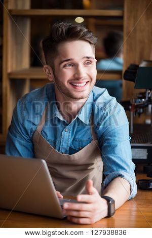 Full of positivity. Cheerful content smiling handsome barista standing at the counter and using laptop while expressing gladness