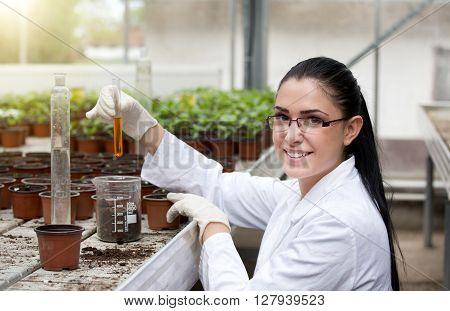 Biloist Holding Test Tube In Greenhouse