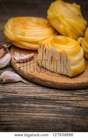 Close up of twisted artisan cheese on wooden board