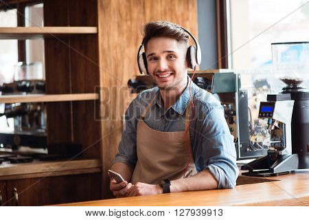 Feel the rhythm. Positive handsome delighted waiter standing at the counter and listening to music while resting at work