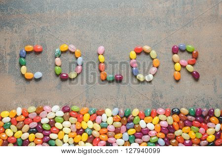 Word color written with jelly beans dark background with colorful border