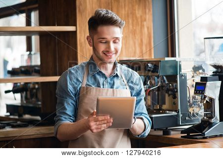 Diligent worker. Pleasant positive handsome smiling waiter using tablet and standing at the counter while being involved in work