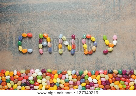 Word candy written with jelly beans dark background with colorful border