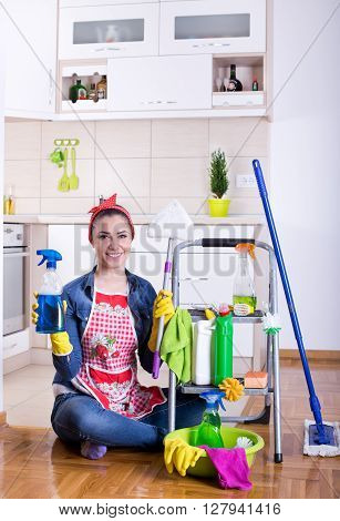 Woman With Cleaning Supplies In The Kitchen