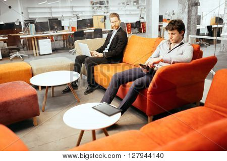 Succesful businesspeople working on devices while relaxing on sofa