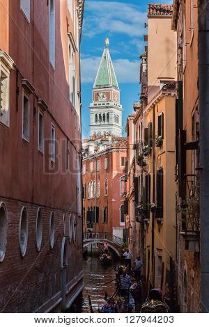 VENEZIA, ITALY - MAY 2015: Typical Narrow Street in Venice and St. Marks Bell Tower - Campanile in Background Venice Italy