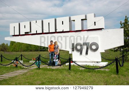 Pripyat, Ukraine - May 9, 2011: Evacuated family poses for photo in front of their hometown name sign in Pripyat, Chernobyl Exclusion Zone, place of Chernobyl nuclear disaster. Every year on May 9 evacuated people are allowed to visit their homes.