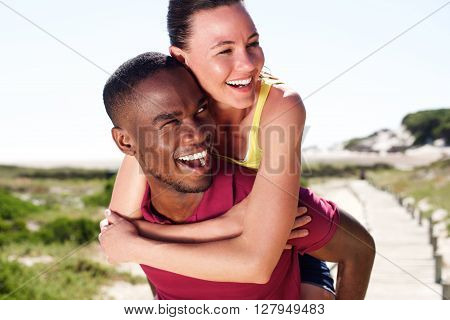 Cheerful Young Man Carrying Beautiful Girlfriend On His Back