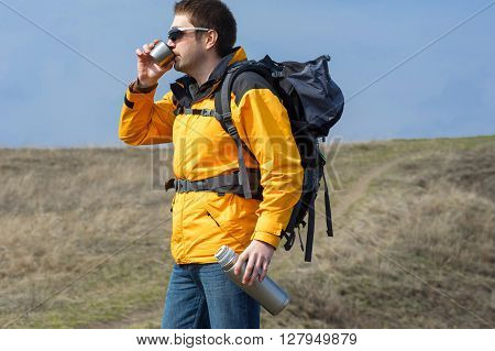 Man Holding Thermos With Hot Tea Outdoors. Hiking And Leisure01