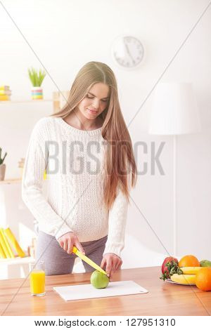 Cute expectant mother is chopping healthy fruit in kitchen. She is standing and smiling