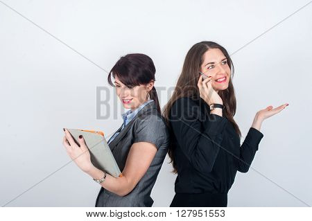 Two business women standing backs to each other and smile. One emotionally talking on the phone and the other works on the tablet