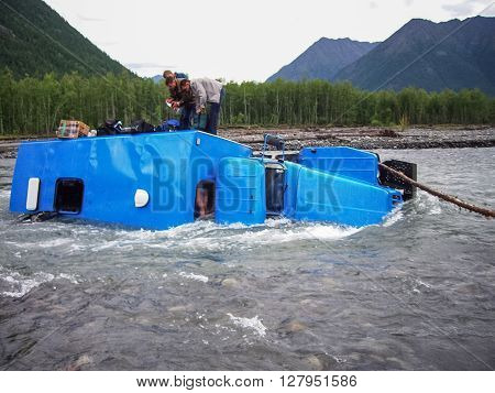 An Accident While Crossing A Mountain Stream. The Car Carrying Workers Overturned And Fell Into The