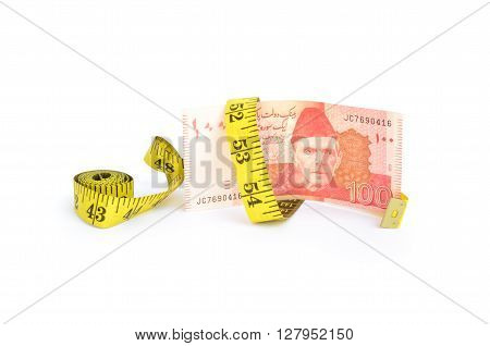 Closeup of hundred rupee Pakistani currency bill wrapped in measure tape for budget cut concepts