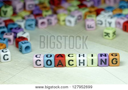 Close up of Coaching word on colorful dices