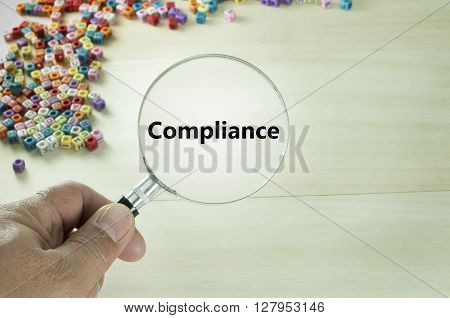 Close up of Compliance text written on magnifying glass