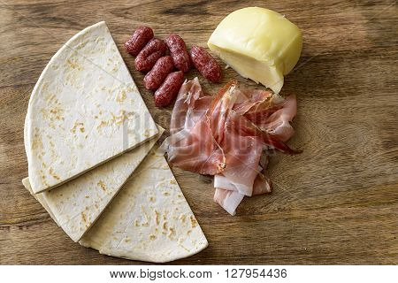 piadina, speck, salami and scamorza on wood