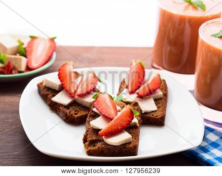 Rye and honey bread slices with tofu cheese and strawberries with strawberry smoothie with tofu for breakfast on dark wooden table