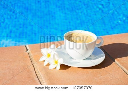white cup of coffee near pool water
