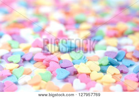 Sugar sprinkle dots, decoration for cake and bakery, a lot of sprinkles in a bucket on white wooden board background