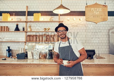 Barista Standing At Bar Counter And Smiling At Camera