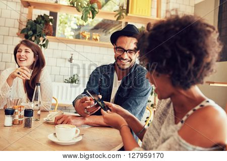 Portrait of young friends talking in cafe and looking at the photos on smart phone. Happy young people having a great time at a restaurant.