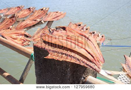 dried fish placed in a rack bamboo tray on sun day light with sea view for sell dry fish in the market