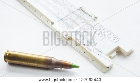Cartridge with a green tip and slide rule on white