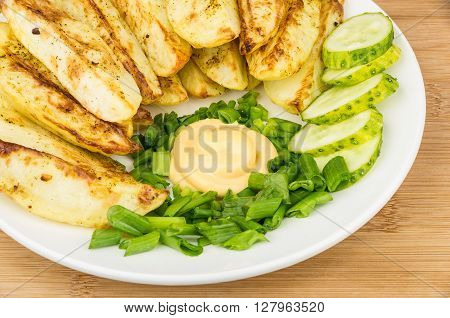 Close up of slices of baked potatoes with mayonnaise and leek