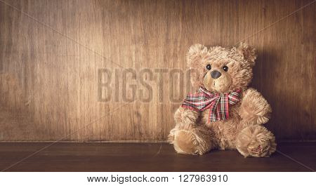 Brown teddy bear on a wooden shelf.