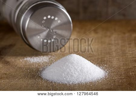 Salt spilling on wooden table from salt cellar