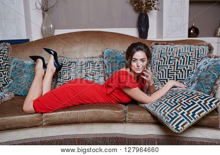 beautiful woman in red dress relaxing on a sofa in luxury interior.
