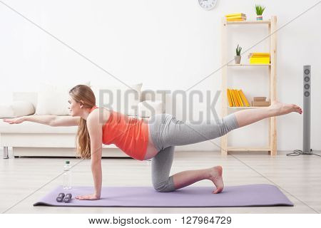 Beautiful young pregnant woman is exercising at home. She is kneeling and smiling. The lady stretching her arm and leg forward
