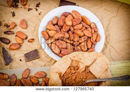 Cacao beans, cocoa powder and black chocolate on table - closeup