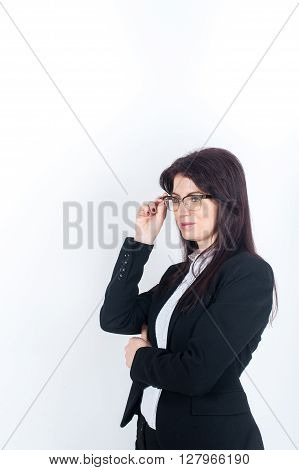 A young dark-haired woman in glasses looking into the distance holding glasses hand