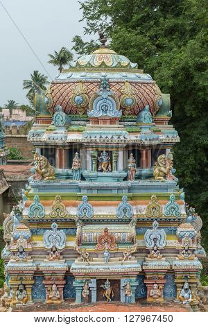 Trichy India - October 15 2013: Statue scenery on shorter Vimanam in older part of Ranganathar Temple. Part built during Madurai Nayak era. Pastel statues of dancers musicians lions and gurus. Green trees and blue skies.