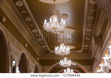 Beautiful glowing chandeliers in the hall of the palace.