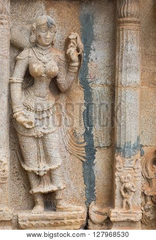 Trichy India - October 15 2013: Sandstone statue of woman with lizard at Ranganathar Temple. Outside wall of old part built during Madurai Nayak era.