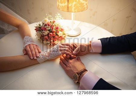 bride and groom are sitting at a table in restaurant. The groom's hand stroking his bride