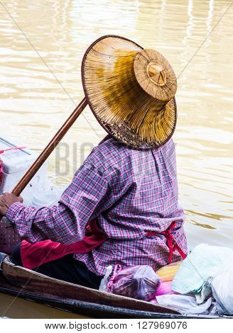 old woman selling food in floating market