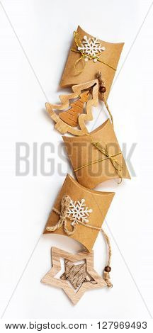 Christmas gifts in kraft paper with a homemade toys on white background.