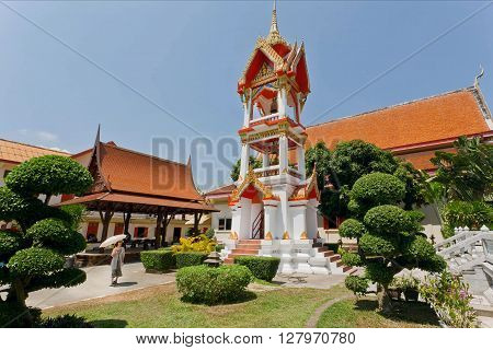 PHUKET, THAILAND - FEB 6, 2016: Woman walking past old bell tower of historical Wat Chalong temple on February 6, 2016. First written mention about the buddhist monastery belongs to 1837