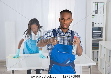 Two Professional Young African Janitors Cleaning Office