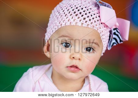 Little baby girl dressed in pink paying attention