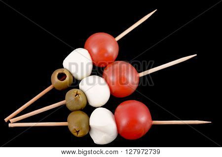 toothpick with olive, mozzarella and tomato  on black background italian flag food