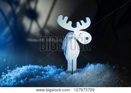 White wooden toy moose in the snow.